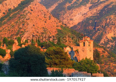 Distant church tower surrounded by mountains at sunset  - stock photo