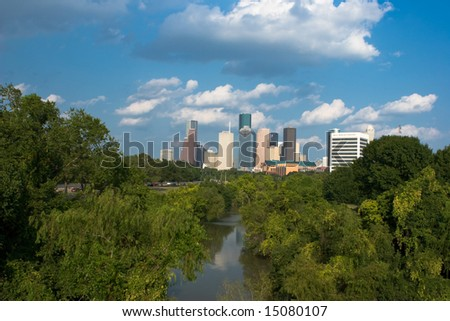 Distant city skyline behind green park with reflections in river - stock photo