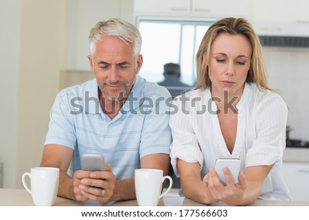 Distant couple sitting at the counter texting and not talking at home in the kitchen - stock photo