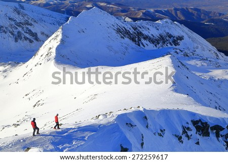 Distant hikers moving on snow covered mountain ridge  - stock photo