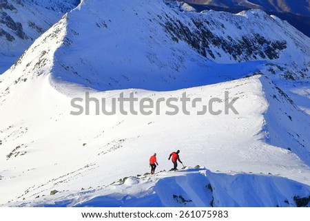 Distant hikers walking on a mountain ridge in winter - stock photo
