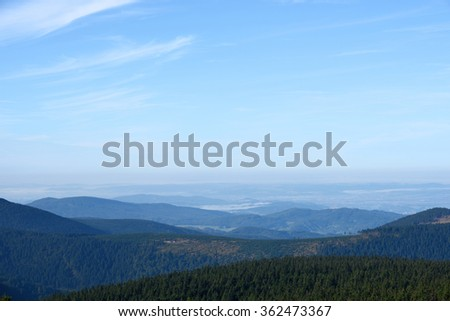 Distant hills and valleys in haze under a blue sky - stock photo