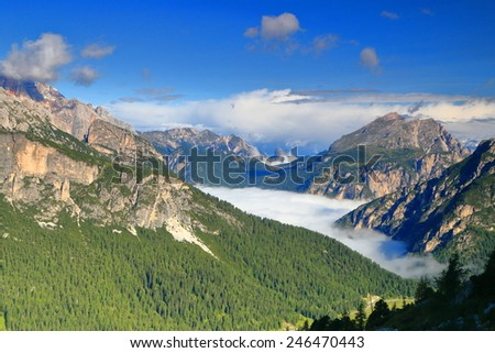 Distant mountains surrounding white clouds abive the valley as seen from Cadini di Misurina, Dolomite Alps, Italy - stock photo