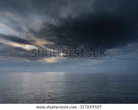 distant off shore wind turbine field set against an early morning background storm cloud sky at sunrise - stock photo