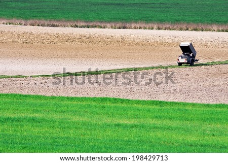 Distant portable air compressor in the agricultural field  - stock photo