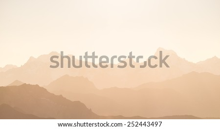 Distant red toned mountain range of the majestic Ecrins Massif National Park, France, arising higher than 4000 m altitude from the alpine arc. Telephoto view at sunset. - stock photo