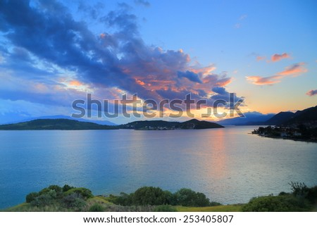 Distant sea and islands under vivid clouds and sky at sunset, Greece - stock photo