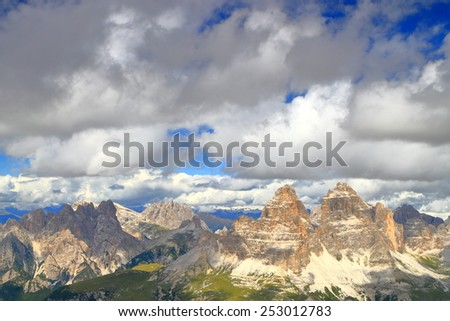 Distant summits of Tre Cime di Lavaredo and large clouds above as seen from Cadini di Misurina, Dolomite Alps, Italy - stock photo