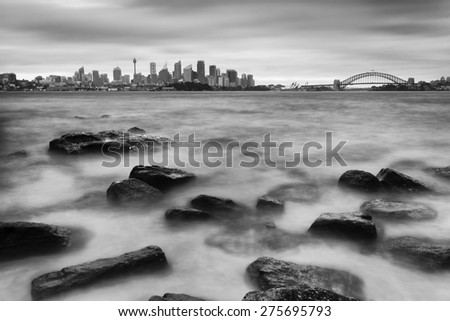 Distant Sydney city CBD landmarks with Harbour Bridge across blurred harbour waters at sunset with beach rocks in foreground - stock photo