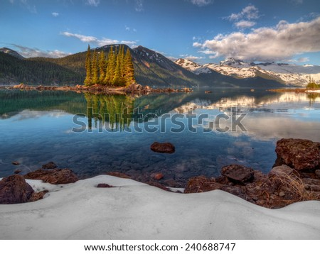 Distant trees in a mountain lake with snow covered lakeside - stock photo