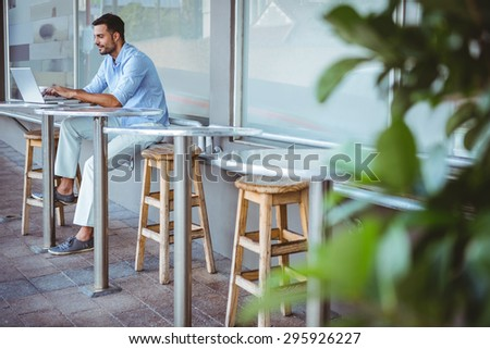 Distant view of a smiling businessman using his laptop outside a cafe - stock photo