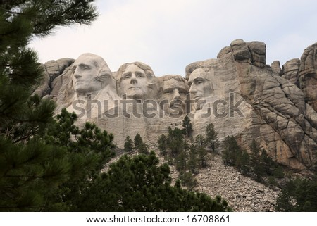 distant view of Mount Rushmore framed by trees - stock photo
