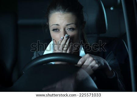 Distracted exhausted woman driving a car late at night. - stock photo