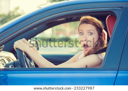 Distracted fright face of a woman driving car, wide open mouth eyes holding wheel side window view. Negative human face expression emotion reaction. Trip risk danger reckless behavior on road concept - stock photo