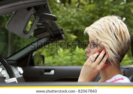 Distracted young woman driving and talking on a mobile phone - stock photo