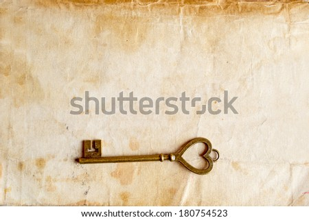 distressed vintage key with old paper texture overlay - stock photo