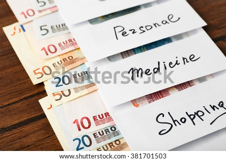 Distribution of money, financial planning, euro in envelopes, on wooden table background - stock photo