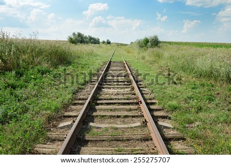 disused railway track on the field - stock photo