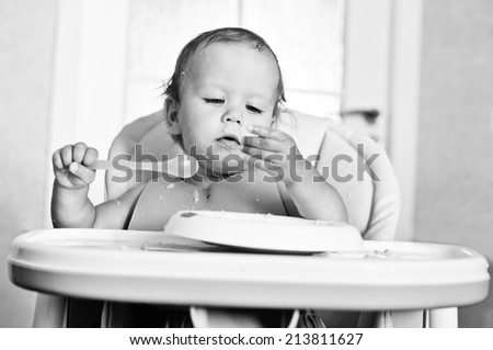 ditry eating baby with spoon - stock photo