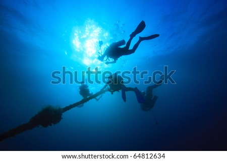 Diver ascend up to sea surface - stock photo