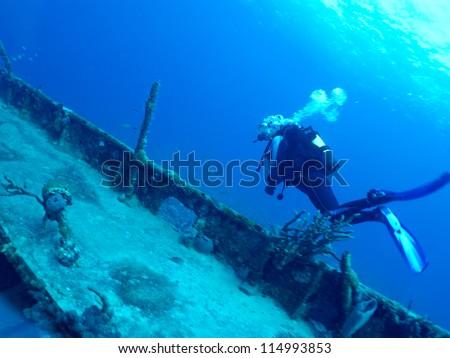 diver explores a wrack - stock photo