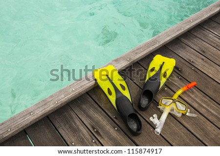 diver eyeglasses, diving goggles, snorkel and fins on the jetty - stock photo