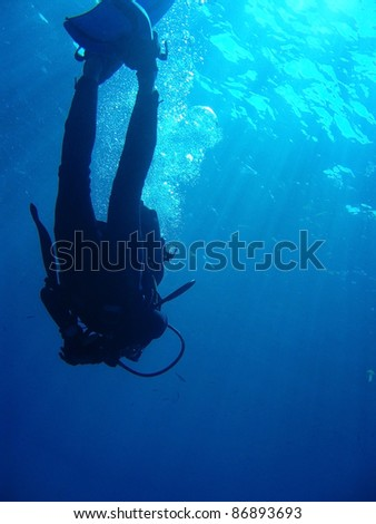 Diver with bubbles and sun rays against surface. There is copy space as well - stock photo