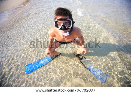 Diver withTube and mask for a scuba diving on seacoast with sand - stock photo
