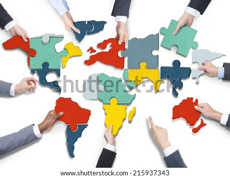 Diverse Business People's Hands with Cartography Puzzle - stock photo