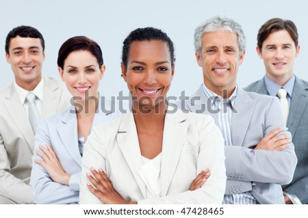 Diverse business people standing with folded arms smiling at the camera - stock photo