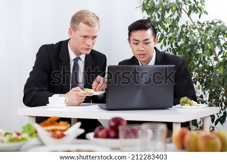 Diverse businessmen working and eating lunch, horizontal - stock photo