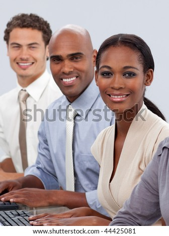 Diverse confident business team sitting in a row smiling at the camera - stock photo