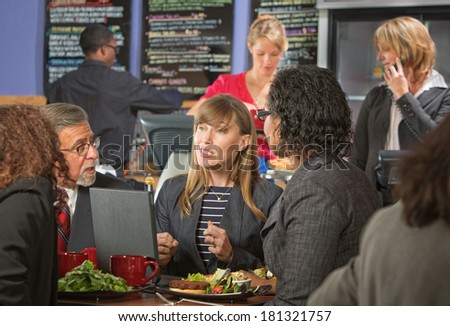 Diverse group of business people eating lunch in cafeteria - stock photo