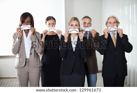 Diverse group of business people holding a card with sad sign by their faces - stock photo