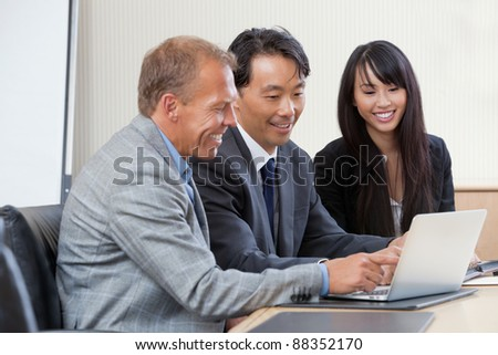 Diverse group of businesspeople working on laptop - stock photo