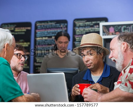 Diverse group of four mature men talking in cafe - stock photo