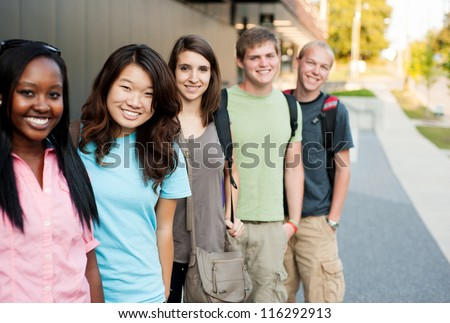 Diverse group of friends in a line smiling - stock photo