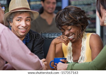 Diverse group of giggling men and women in coffee house - stock photo