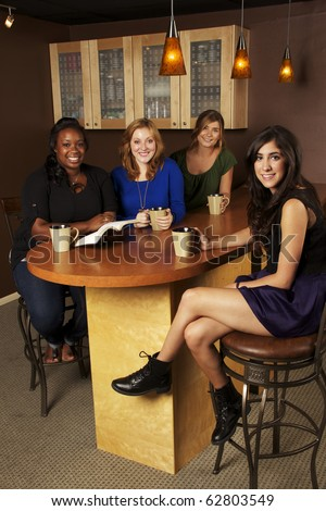 Diverse group of Girlfriends reading the Bible at a Cafe - stock photo