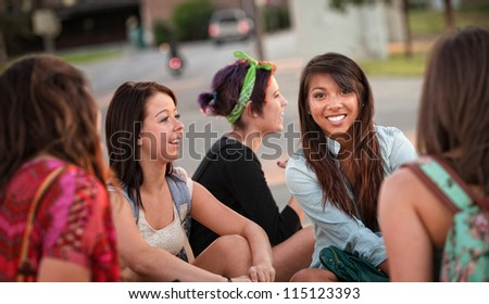 Diverse group of happy teenage girls sitting and talking - stock photo