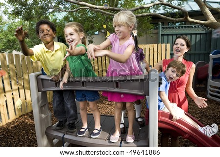 Diverse group of preschool 5 year old children playing in daycare with teacher - stock photo