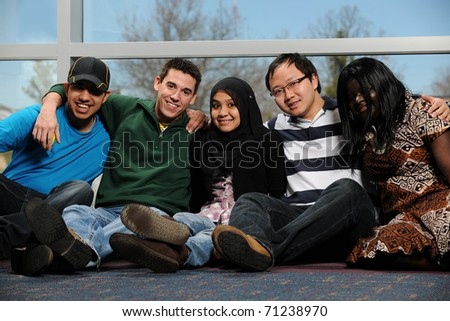 Diverse Group of Students smiling by a window - stock photo