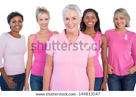 Diverse group of women wearing pink tops and breast cancer ribbons on white background - stock photo
