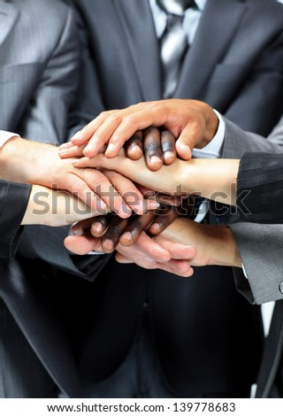 diverse group of workers with their hands together in form of teamwork - stock photo