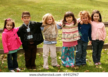 diverse group of young kids standing outside in fall - stock photo