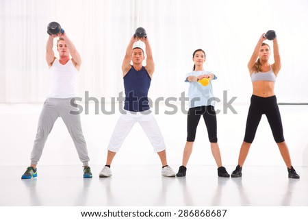 Diverse group practicing kettlebell exercise in crossfit gym - stock photo