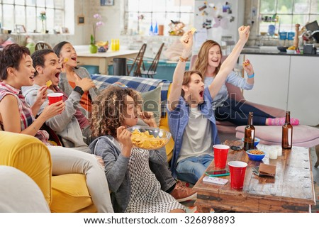 Diverse mix of friends sports fans watching winning football match on TV at home Celebrating winning goal huddled on couch shouting excited  sharing snacks drinking beer - stock photo