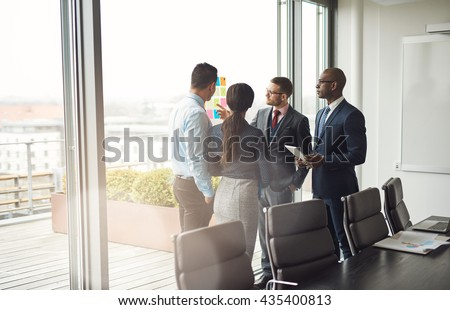 Diverse multiracial management team standing grouped in front of a large bright window in the conference room discussing colorful memos on the glass - stock photo