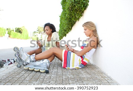 Diverse teenager friends sitting together in a suburban street using their smart phones wearing roller blades, sporty lifestyle. African american and caucasian adolescents with technology outdoors. - stock photo