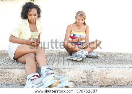 Diverse teenager friends sitting together smiling in a street using their smart phones wearing roller blades, sporty lifestyle. African american and caucasian adolescents with technology outdoors. - stock photo
